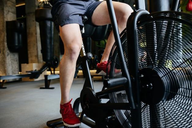 Beschnittenes bild des muskulösen mannes unter verwendung des sich drehenden fahrrads