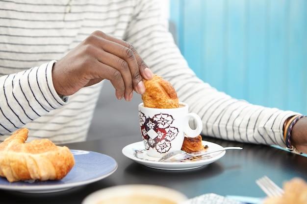 Beschnittenes bild des nicht wiedererkennbaren afroamerikanischen mannes, der croissant in tasse cappuccino eintaucht, köstliches frühstück allein im café genießt, am tisch mit becher und gebäck sitzt. filmeffekt