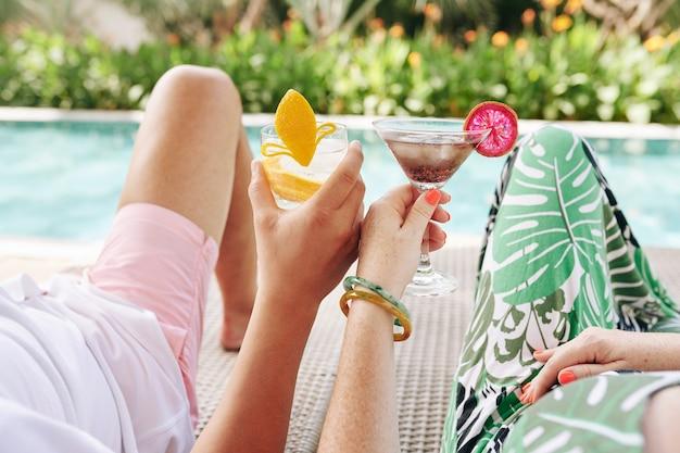 Beschnittenes bild des paares, das cocktails trinkt, wenn man sich auf chaiselongues am swimmingpool entspannt