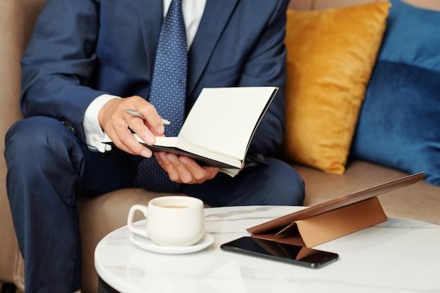 Beschnittenes bild des planers, der geschäftsmann prüft, bevor er online-treffen mit kollegen oder geschäftspartnern hat