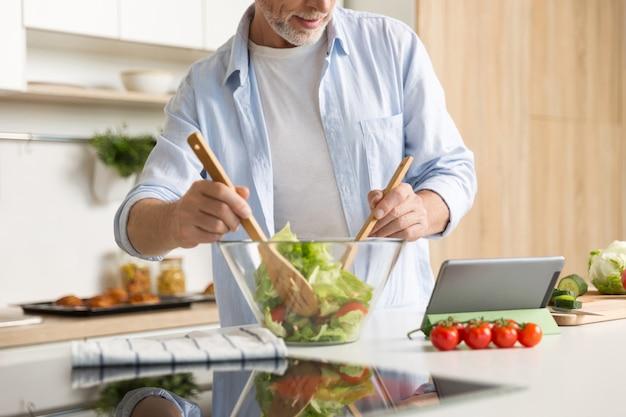 Beschnittenes bild des reifen mannes, der salat unter verwendung der tablette kocht