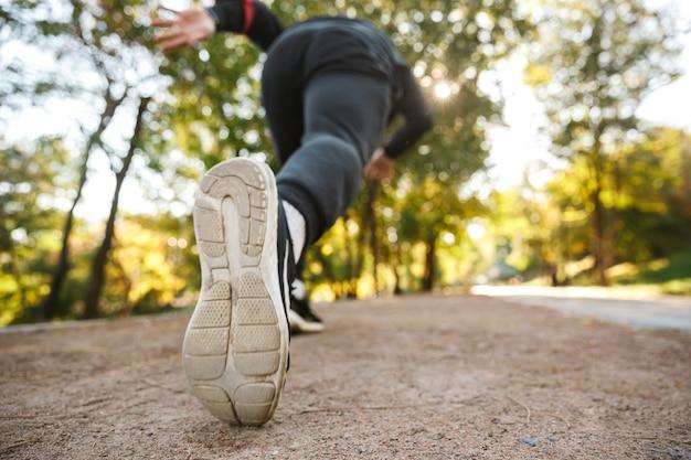 Beschnittenes bild des schönen jungen sportfitnessmannläufers draußen im park.