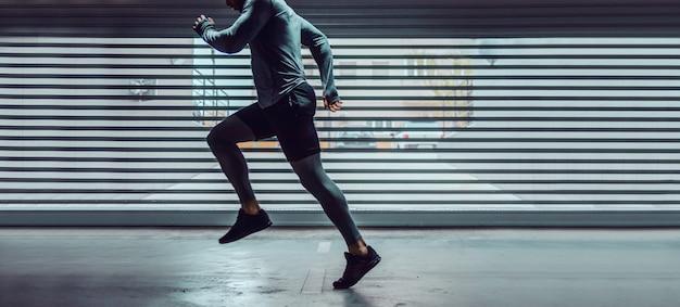 Beschnittenes bild des schönen kaukasischen sportlers in der aktiven kleidung, die in der tiefgarage läuft. konzept des städtischen lebens.