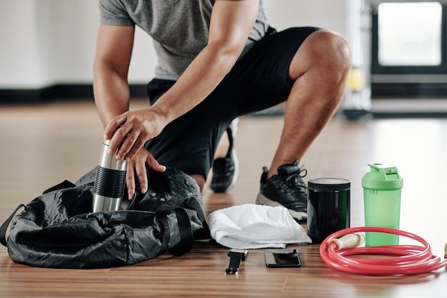 Beschnittenes bild des sportmanns, der tasche auf turnhallenboden nach dem training packt