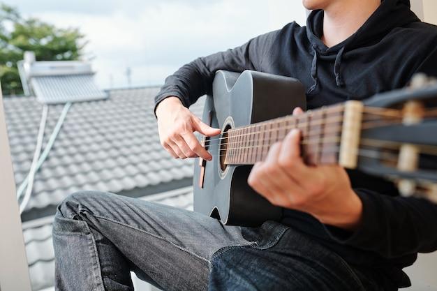 Beschnittenes bild des teenagers, der auf fensterbank sitzt und gitarre spielt
