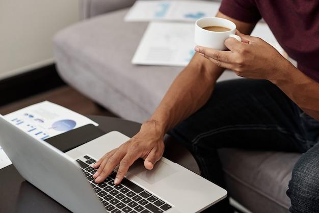 Beschnittenes bild des unternehmers, der eine tasse kaffee trinkt, wenn er e-mails von kunden beantwortet