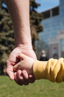 Beschnittenes bild des vaters, der hand seines kleinen sohnes hält