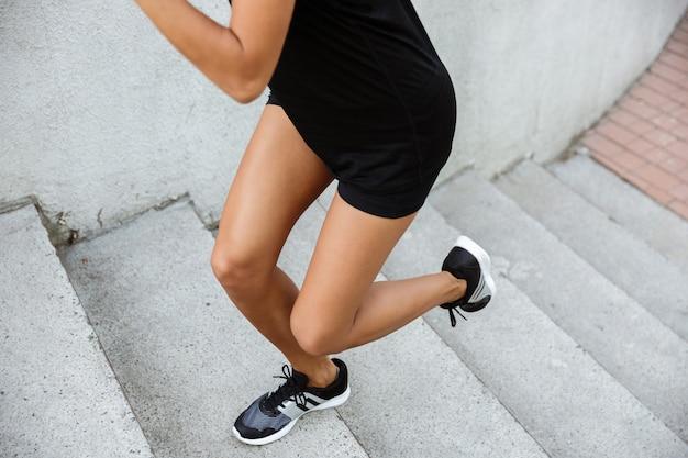 Beschnittenes bild einer fitnessfrau, die die treppe hinaufläuft