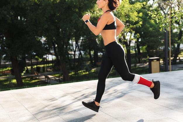 Beschnittenes bild einer fitnessfrau, die sportkleidung trägt, die draußen läuft