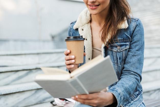 Beschnittenes bild einer lächelnden jungen frau, die jacke trägt, die draußen auf einer bank sitzt, buch liest und tasse kaffee zum mitnehmen hält