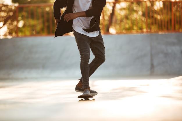 Beschnittenes bild eines afrikanischen skateboarder-eislaufens