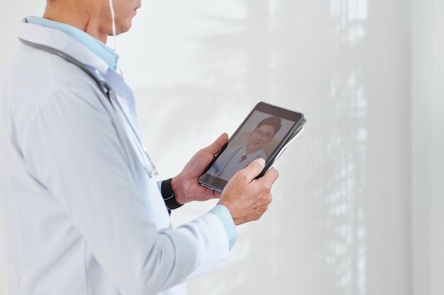Beschnittenes bild eines arztvideos, das seinen kollegen über einen tablet-computer anruft