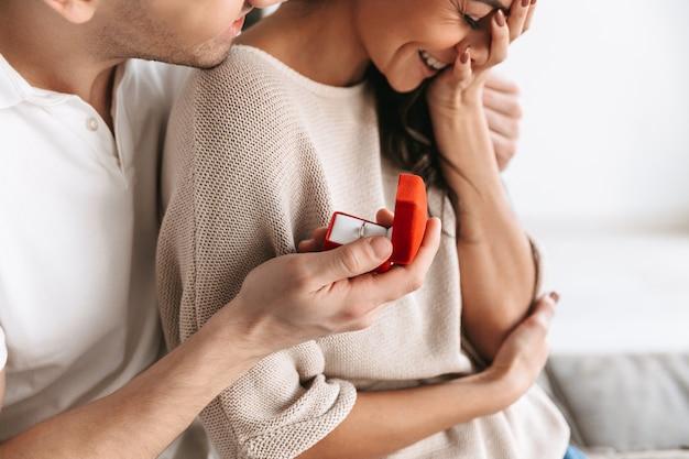 Beschnittenes bild eines glücklichen jungen mannes, der seiner freundin einen vorschlag mit einem ring in einer schachtel zu hause macht