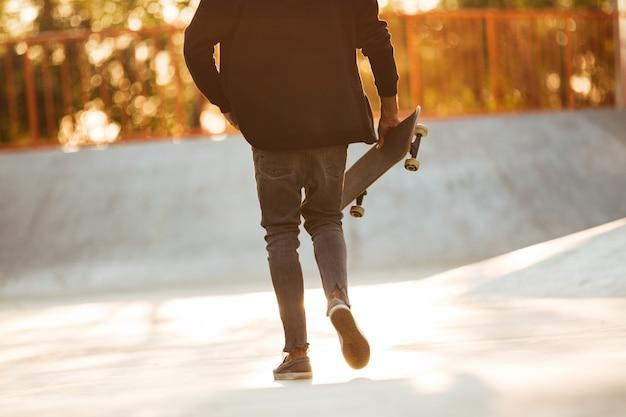 Beschnittenes bild eines jungen afrikanischen mannskateboarders, der geht
