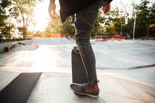 Beschnittenes bild eines jungen männlichen teenagers, der ein skateboard reitet