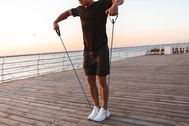 Beschnittenes bild eines jungen sportlers, der übungen macht