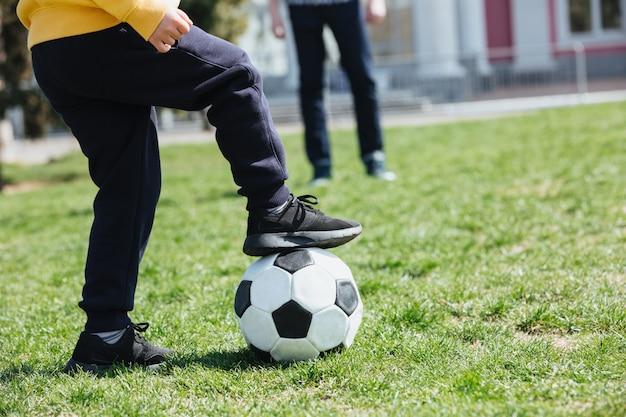 Beschnittenes bild eines kleinen jungen mit fußballspiel