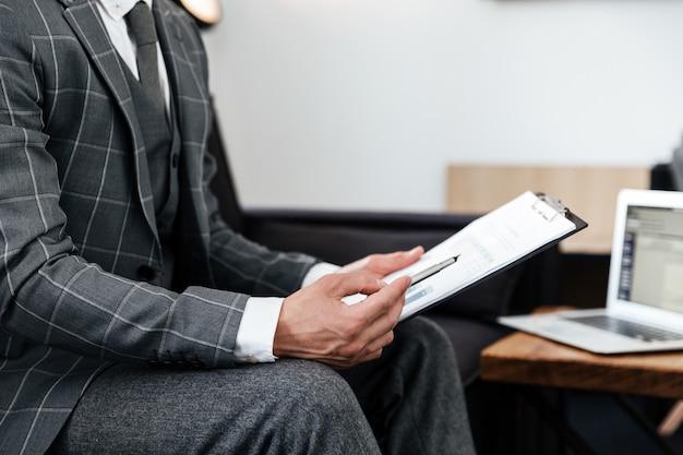 Beschnittenes bild eines mannes im anzug, der dokumente analysiert