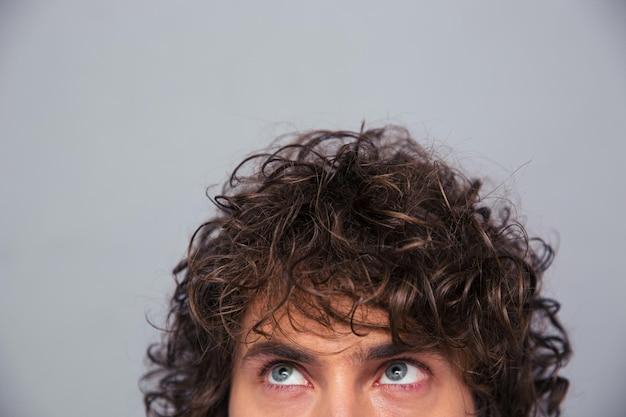 Beschnittenes bild eines mannes mit dem lockigen haar, der oben auf copyspace über graue wand schaut