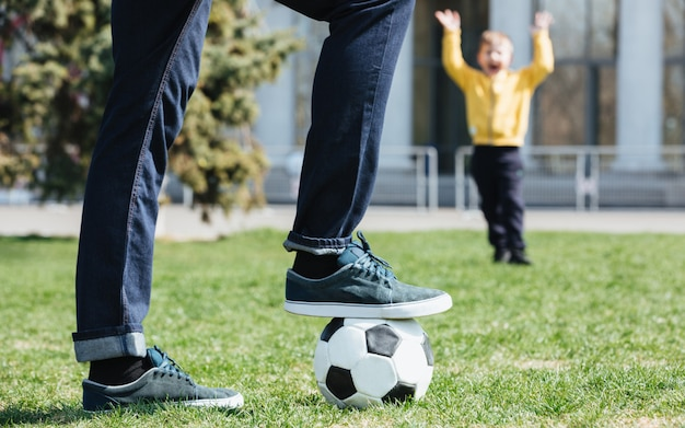 Beschnittenes bild eines vaters, der mit seinem sohn fußball spielt