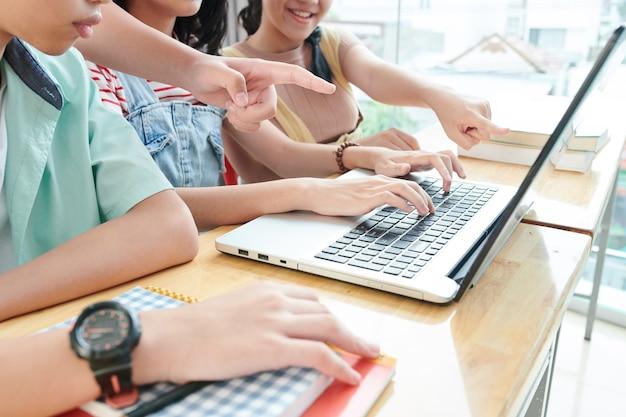 Beschnittenes bild von schülern, die sich am laptop versammelt haben, um gemeinsam an einem schulprojekt zu arbeiten