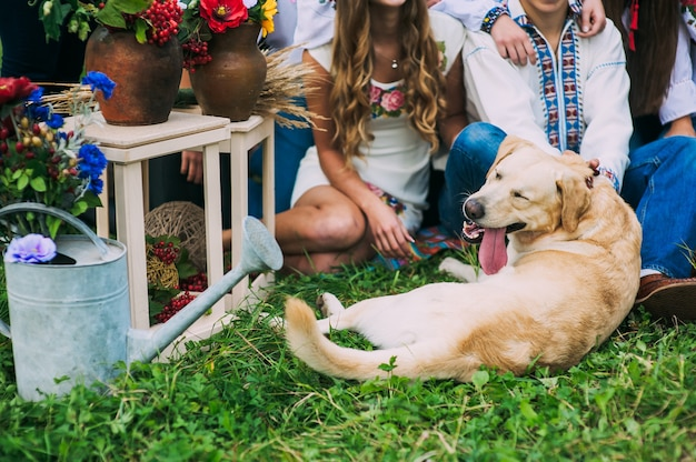 Beschnittenes bildporträt eines hellhaarigen hundes mit einer hervorstehenden zunge nahe leuten, die in einem ländlichen dekor im ukrainischen stil fotografiert werden. helle farben, getöntes bild.