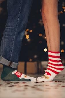 Beschnittenes foto der beine von mann und frau in warmen weihnachtssocken. urlaubskonzept