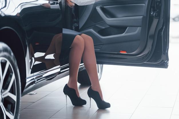 Beschnittenes foto der frau in den schwarzen hohen absätzen, die im auto sitzen