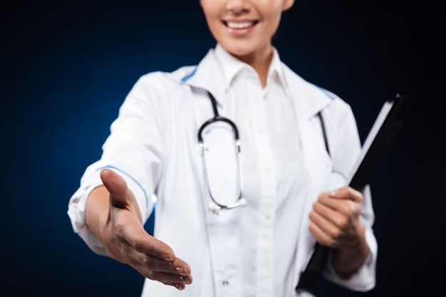 Beschnittenes foto der fröhlichen krankenschwester, die zwischenablage hält und hand ausstreckt