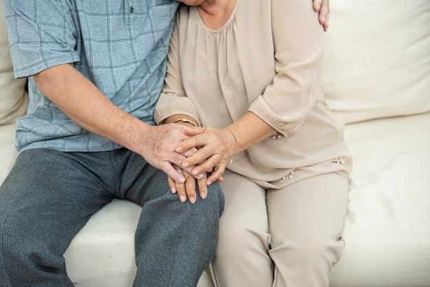 Beschnittenes foto der hände des niedlichen älteren älteren asiatischen paares, das hände mit liebe auf sofa hält. alte leute umarmen und händchen haltend. paar konzept. liebevolles konzept. fürsorgliches konzept.