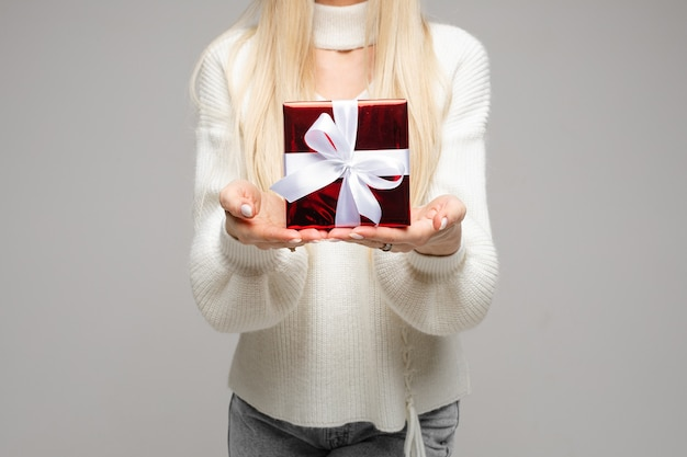 Beschnittenes foto der jungen frau, die rote box zeigt, während weihnachten feiert