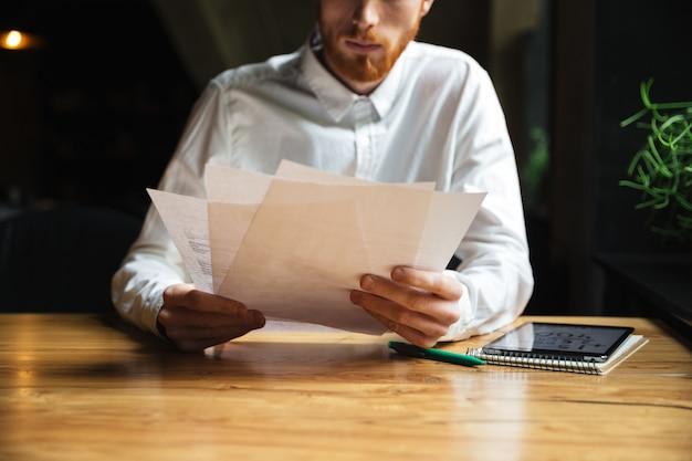 Beschnittenes foto des bärtigen mannes des jungen lesekopfes, der mit papieren arbeitet