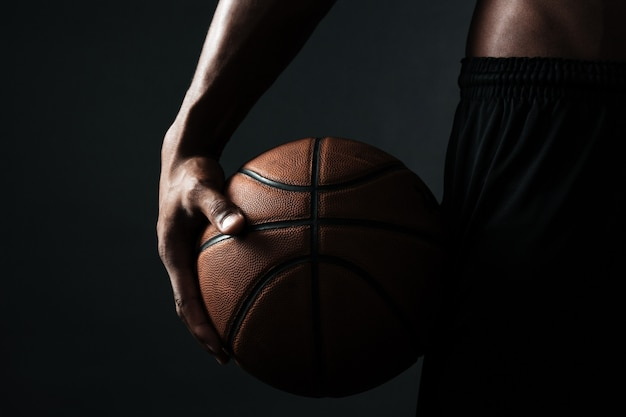 Beschnittenes foto des basketballspielers, der ball hält