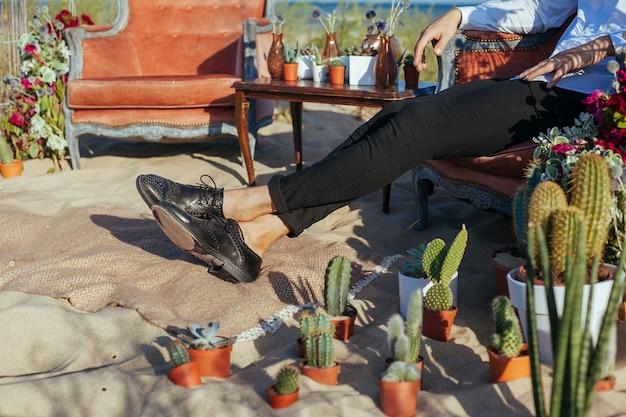 Beschnittenes foto des bräutigams, der auf dem stuhl auf der hochzeitszeremonie am strand sitzt.