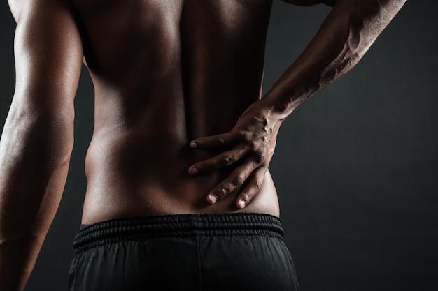 Beschnittenes foto des jungen afroamerikanischen mannes mit rückenschmerzen