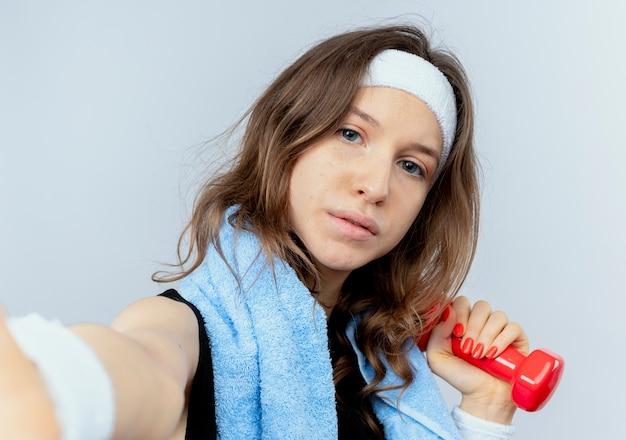 Beschnittenes foto des jungen fitnessmädchens mit stirnband und handtuch um den hals, das hantel in der hand mit ernstem gesicht über weißer wand hält