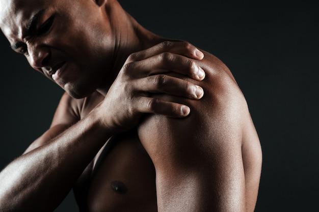 Beschnittenes foto des jungen hemdlosen afroamerikanischen mannes mit schulterschmerzen