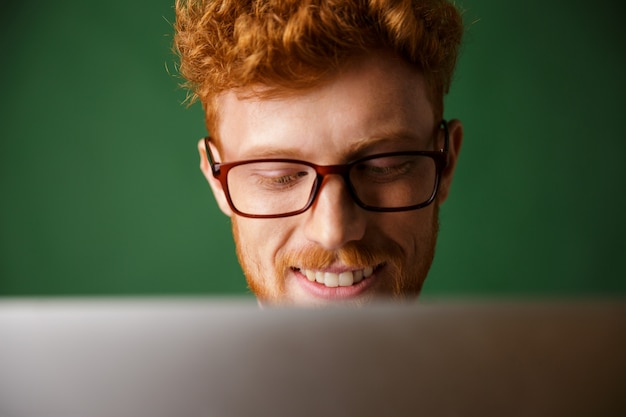 Beschnittenes foto des jungen lesekopfmannes in den gläsern, die mit laptop arbeiten