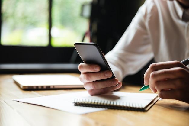 Beschnittenes foto des jungen mannes im weißen hemd, das smartphone hält, während nach papierkram ruht