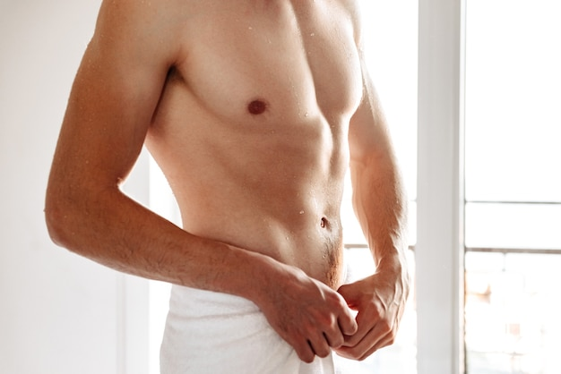 Beschnittenes foto des jungen nackten mannes mit handtuch.