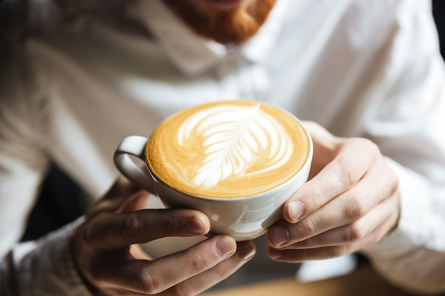 Beschnittenes foto des mannes im weißen hemd, das heiße kaffeetasse hält