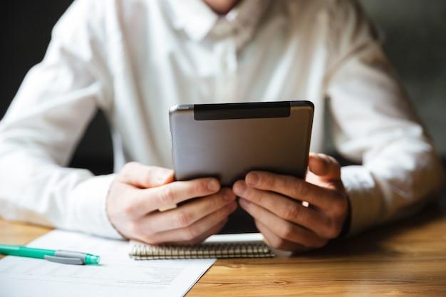 Beschnittenes foto des mannes im weißen hemd unter verwendung der digitalen tablette