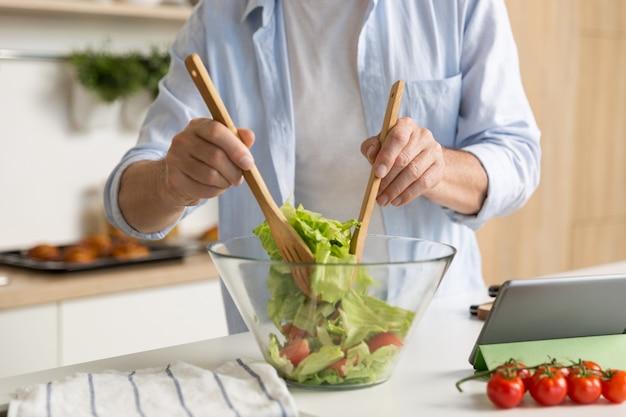 Beschnittenes foto des reifen mannes, der salat kocht