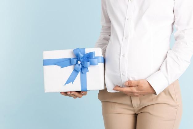 Beschnittenes foto einer jungen schwangeren frau lokalisiert, die geschenkbox hält.