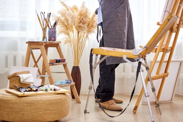 Beschnittenes foto eines männlichen künstlers bei der arbeit im studio, notwendige ausrüstungswerkzeuge und materialien, die für die erstellung von gemälden im hellen raum benötigt werden