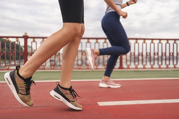 Beschnittenes foto von jungen sportlerinnen, die am morgen auf der brücke in der stadt trainieren