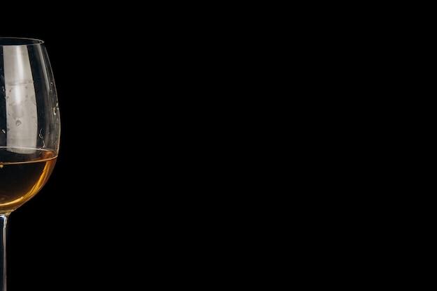Beschnittenes glas weißwein auf einem schwarzen hintergrund. nahaufnahme des alkoholischen getränks.