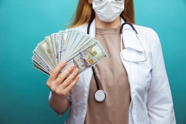 Beschnittenes nahaufnahmefoto der ärztin, die banknoten in ihren händen lokalisiert über blau hält.
