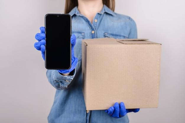 Beschnittenes nahaufnahmefoto der hand, die touchscreen demonstriert und pappkarton über graue wand isoliert hält