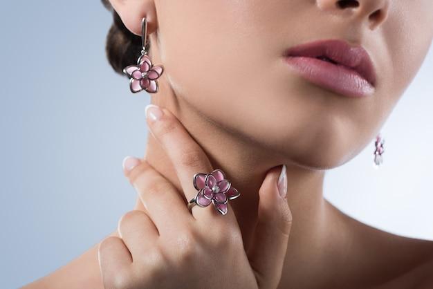 Beschnittenes nahaufnahmeporträt eines jungen modells, das sinnlich tragenden blumenförmigen ring und ohrringe aufwirft